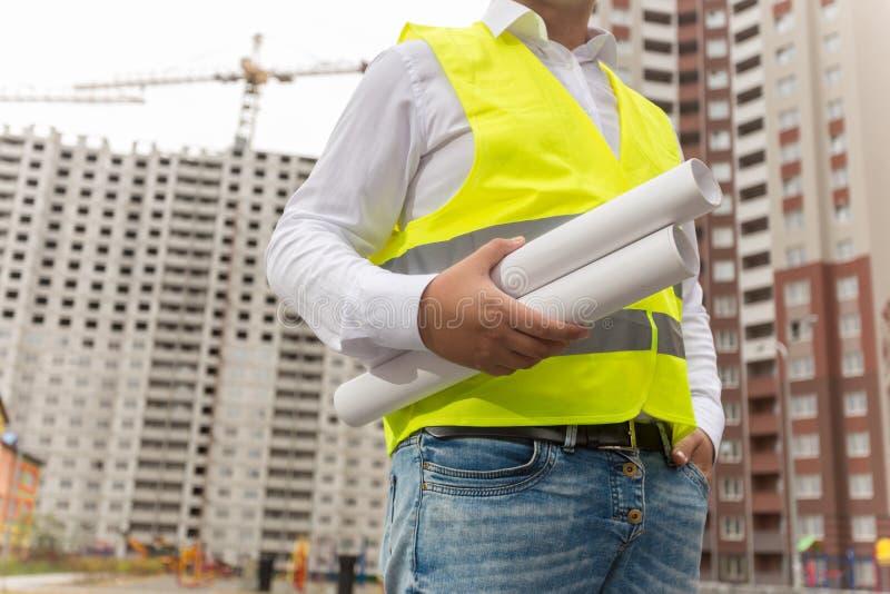 Image de plan rapproché de l'architecte masculin tenant des modèles de nouvelle maison contre le chantier photo libre de droits
