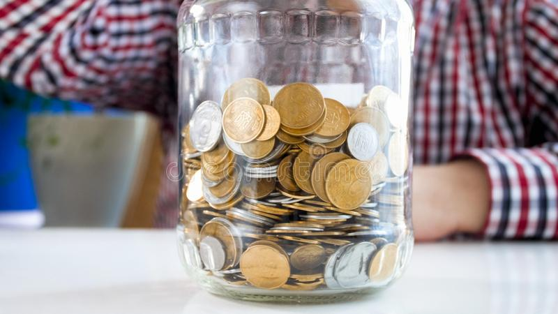 Image de plan rapproché de l'homme se reposant avec le pot en verre plein des pièces de monnaie d'or image stock
