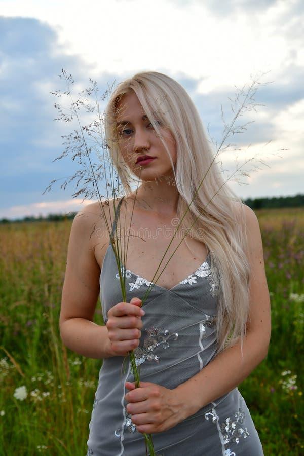 Image de plan rapproché de la dame songeuse blonde parfaite détendant sur le tas du foin en été photos libres de droits