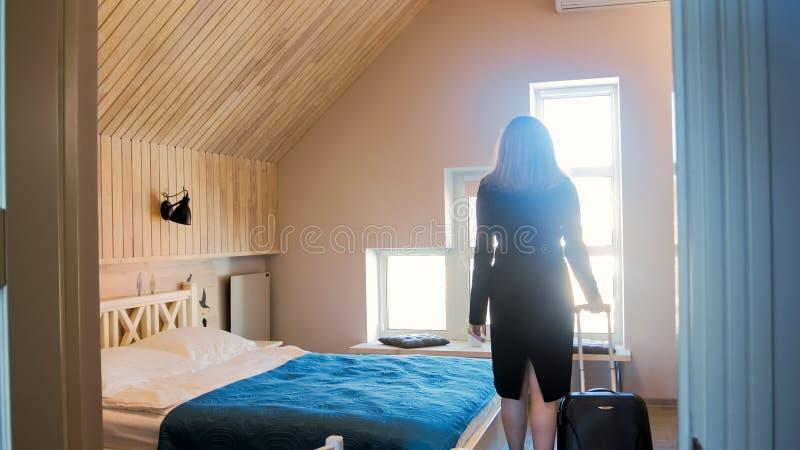 Image de silhouette de vue arrière de jeune femme avec la chambre d'hôtel enetering de valise avec la grande fenêtre photo libre de droits