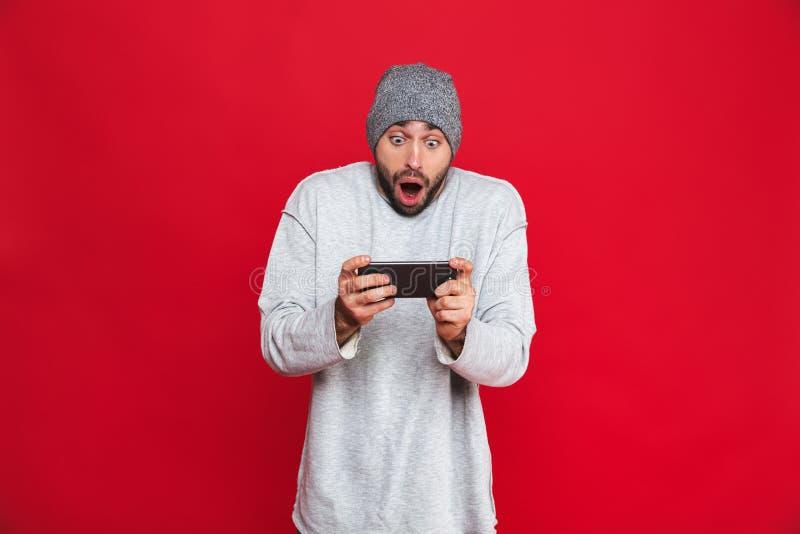 Image de smartphone enthousiaste de participation de l'homme 30s et de jeux vidéo de jeu, d'isolement au-dessus du fond rouge photo stock