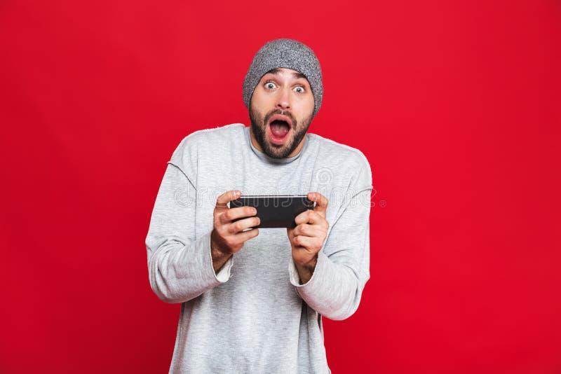 Image de smartphone de participation de l'homme 30s et de jeux vidéo étonnés de jeu, d'isolement au-dessus du fond rouge images libres de droits