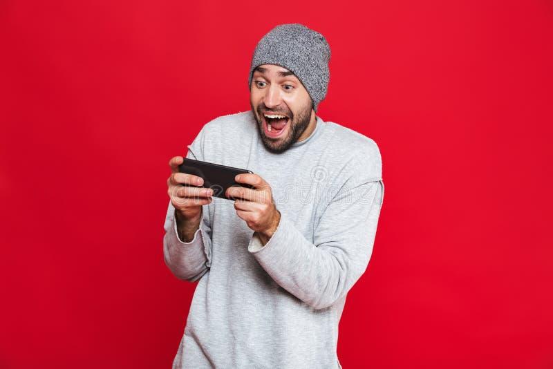 Image de smartphone de participation de l'homme 30s et de jeux vidéo européens de jeu, au-dessus de fond rouge photos stock