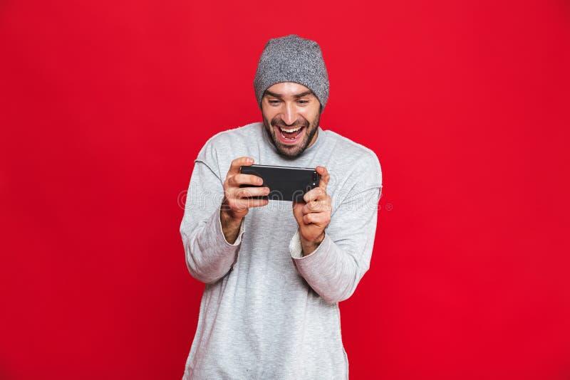 Image de smartphone de participation de l'homme 30s et de jeux vidéo joyeux de jeu, d'isolement au-dessus du fond rouge photographie stock libre de droits