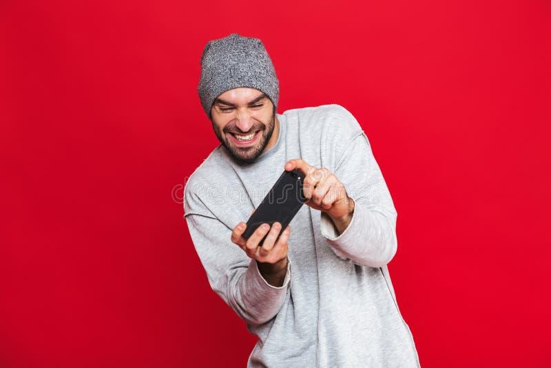 Image de smartphone de participation de l'homme 30s et de jeux vidéo positifs de jeu, d'isolement au-dessus du fond rouge photographie stock
