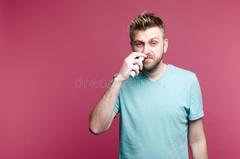 Image de studio d'un pulvérisateur de nez d'utilisations de jeune homme Le type malade d'isolement a l'?coulement nasal l'homme p images libres de droits