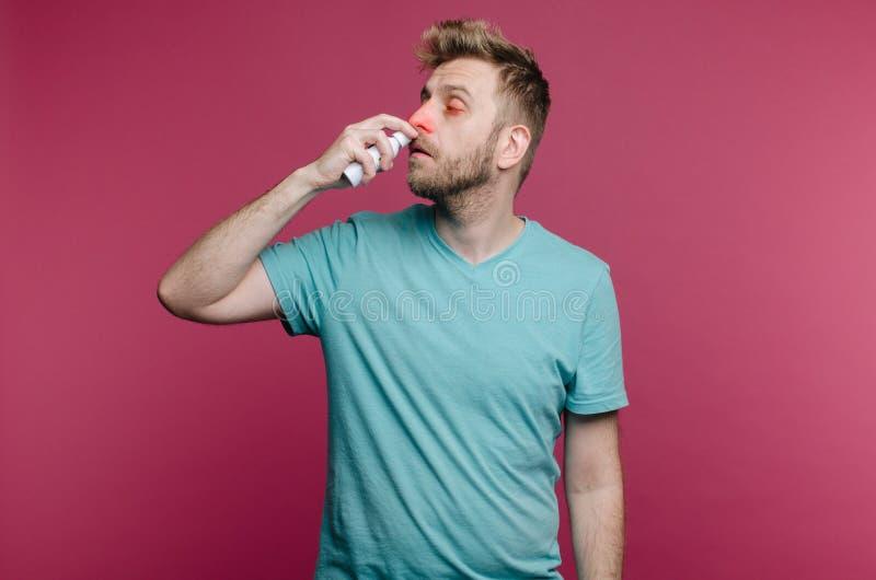image de studio d'un pulvérisateur de nez d'utilisations de jeune homme photographie stock libre de droits