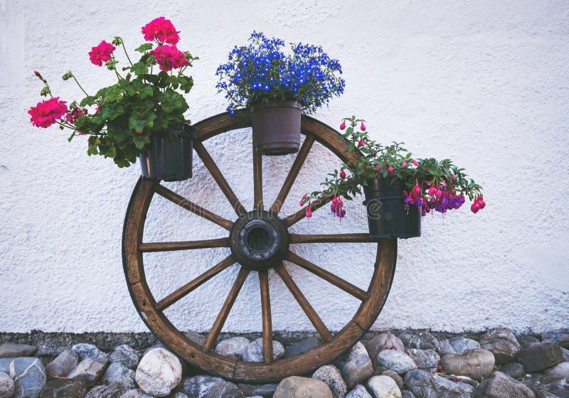Image de style de vintage de pot de fleur avec la roue en bois photo stock