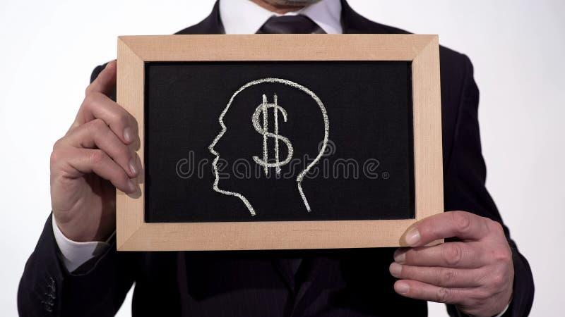 Image de tête de symbole du dollar sur le tableau noir dans des mains d'homme d'affaires, avidité pour l'argent photo stock