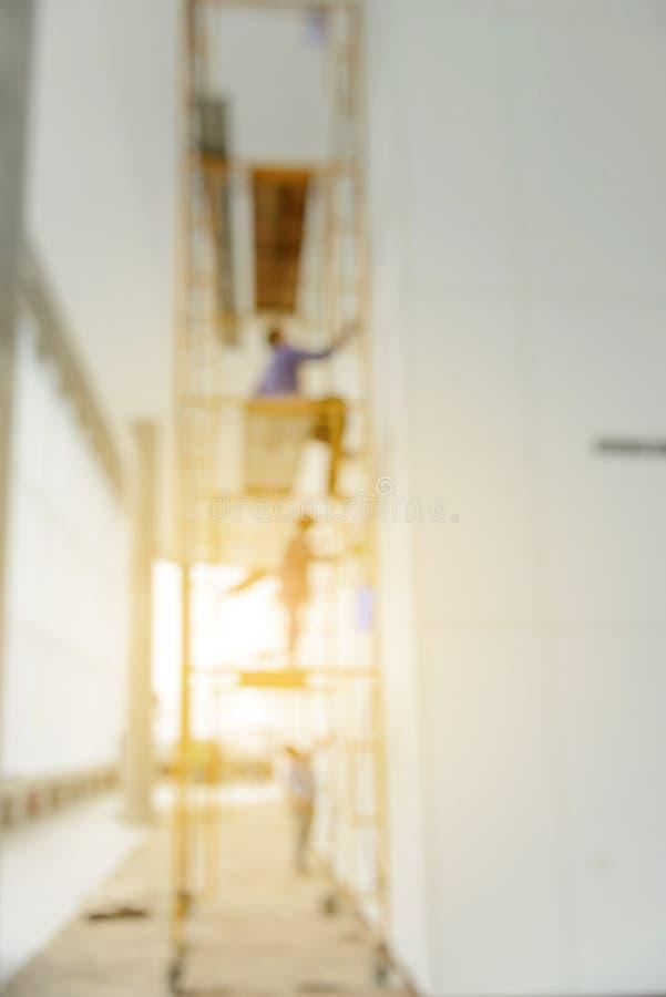 Image de tache floue abstraite de trois travailleurs travaillant à l'échafaudage photo stock