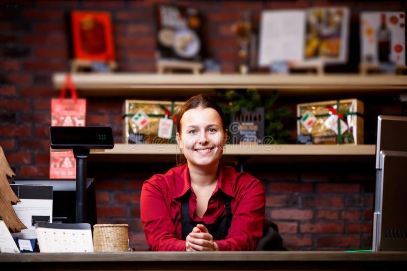 Image de vendeuse de femme dans la position noire de tablier derrière le caissier images stock