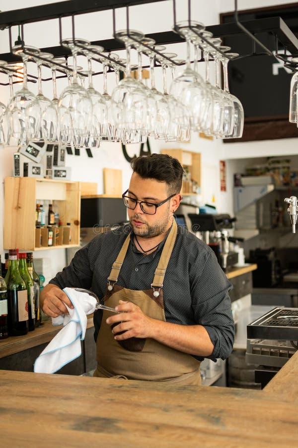 Image de verre de vin de nettoyage de serveur dans un bar photos stock
