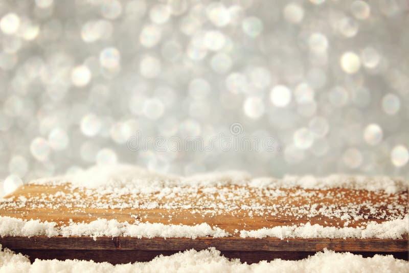 Image de vieille table en bois et de neige fraîche de décembre sur le dessus devant le fond de scintillement Foyer sélectif photo libre de droits