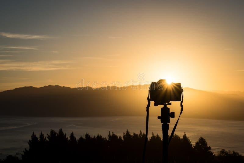 Image de voyage d'une installation de caméra pour tirer le coucher du soleil sur une colline au Nouvelle-Zélande photographie stock