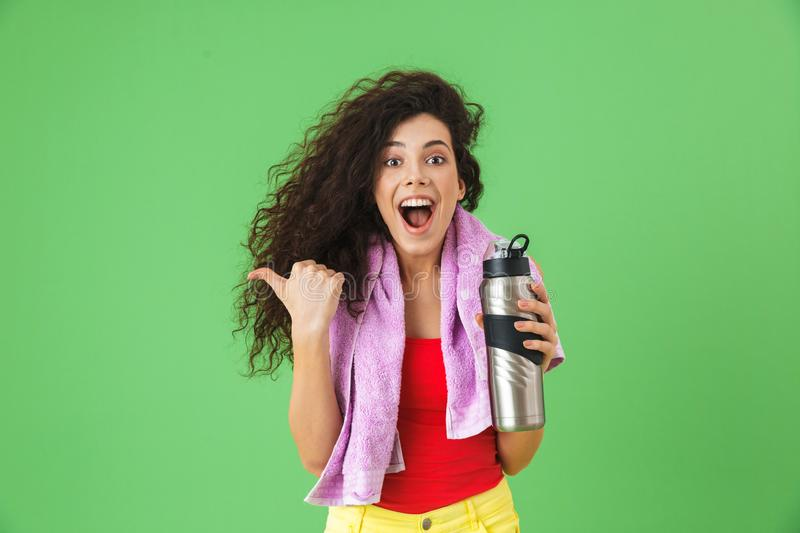 Image of delighted woman 20s in sportswear rejoicing and drinking water after training stock photography