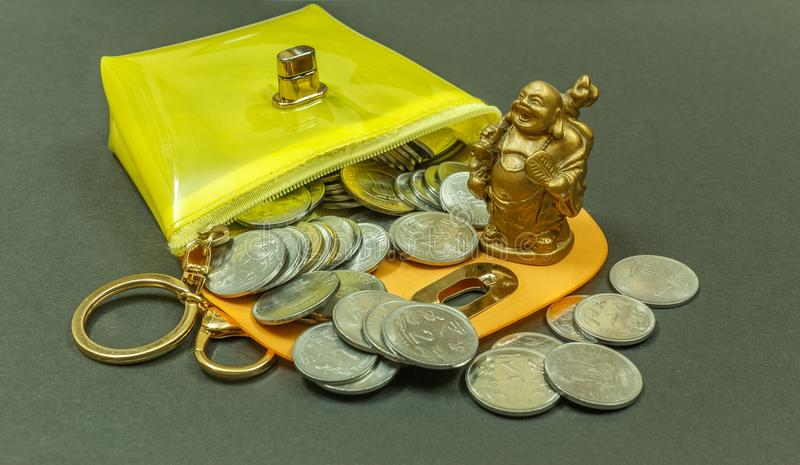 IMAGE DEPICTING THE FINANCIAL SITUATION SEEN WITH COINS INSIDE A PURSE WITH LAUGHING BUDDHA. WITH SELECTIVE FOCUS ON THE SUBJECT. stock photos