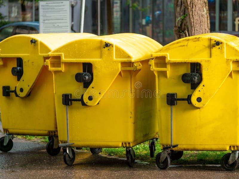 Image des bacs à vidange jaunes, bac de recyclage pour les déchets spéciaux, par la grêle et le temps pluvieux photographie stock