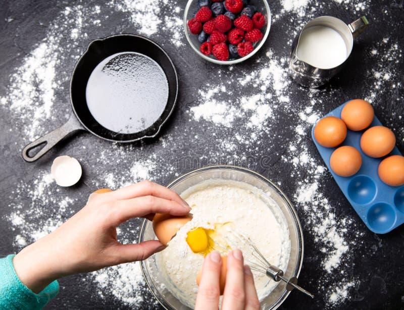 Image des mains de l'homme cassant des oeufs dans la cuvette Tableau avec des baies, lait, farine image stock