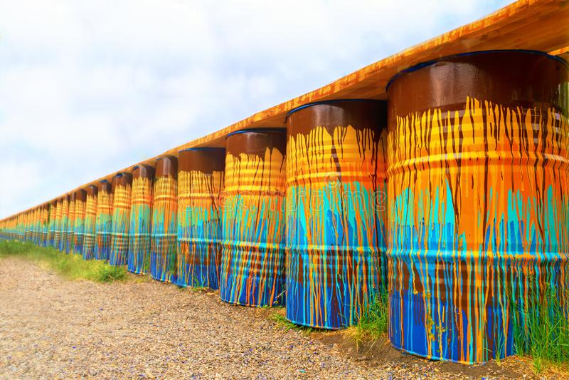 Image des tonneaux à huile multicolores, rouillés et vieux dans les piles avec un ciel bleu et un jour ensoleillé perspective de  images stock