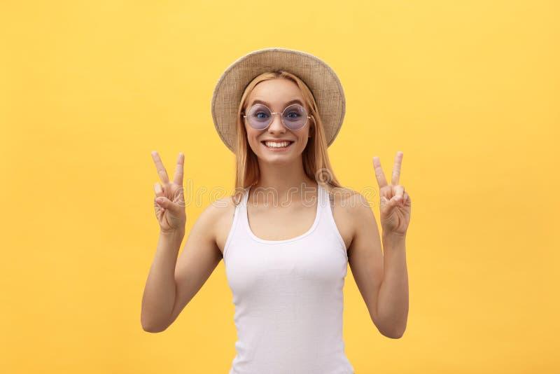 Image des vêtements décontractés de port de femme caucasienne gaie souriant et montrant le signe de paix avec deux doigts plus de photographie stock