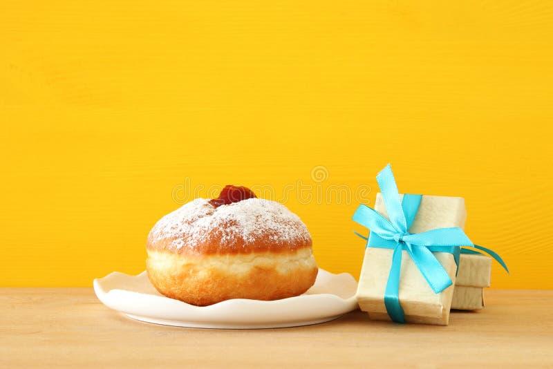 Image des vacances juives Hanoucca avec la boîte et le beignet actuels sur la table