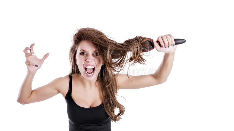 Image of desperate beautiful woman shouts angrily, cant make hairstyle, being angry with comb. hair healt concept royalty free stock images