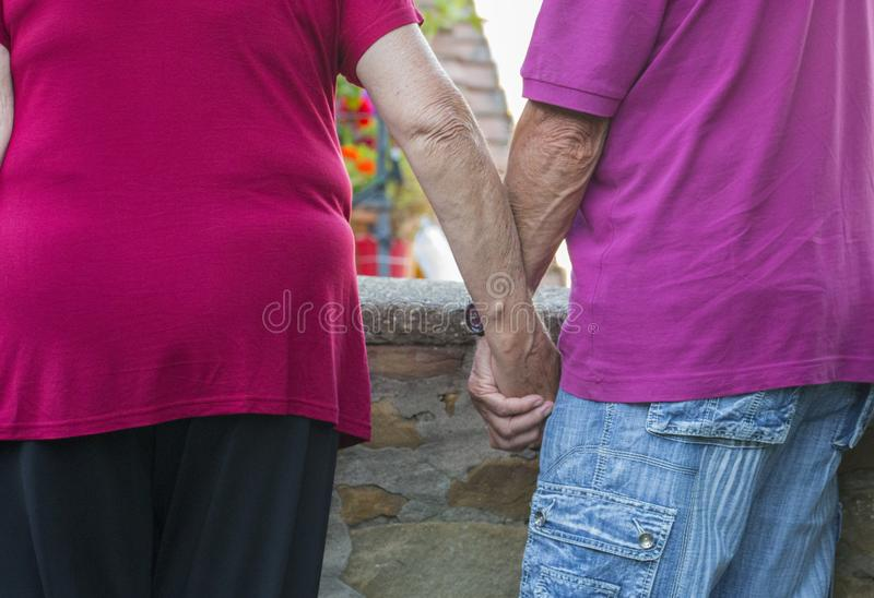 Image with detail of an elderly couple man and woman holding eac. H other`s hand with background stock photo