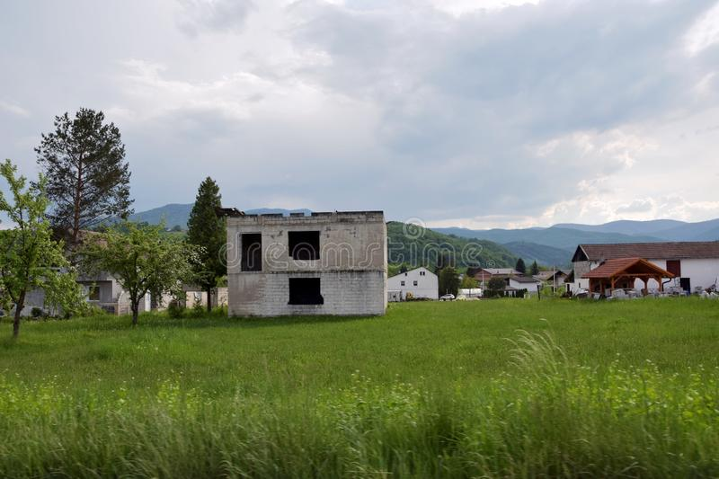 Image of devastated unfinished house structure in rural village area stock photo