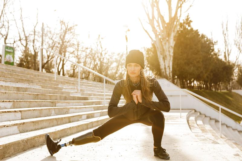 Image of disabled running girl in sportswear, doing sit ups and stock photography