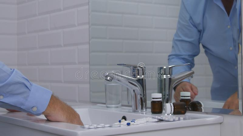 Disappointed Person Image in Bathroom Taking Pills and Drugs. Image with Disappointed and Suffering Businessperson in Bathroom Taking Pills and Drugs stock images
