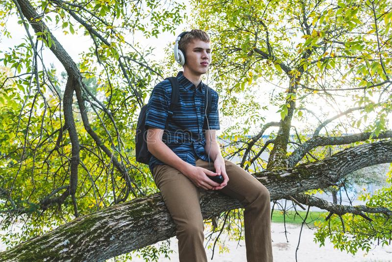 Contemplative student listening to music. The image displays a contemplative student sitting on a tree branch while listening to music through his headphones stock image