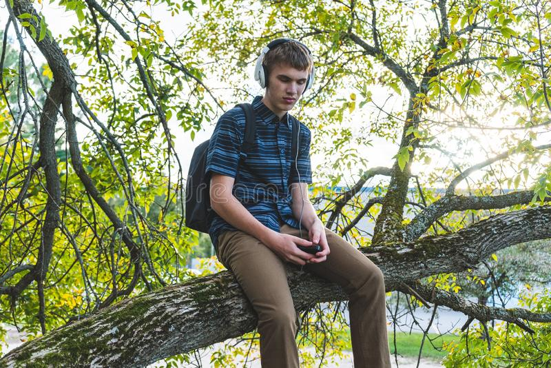 Contemplative student listening to music. The image displays a contemplative student sitting on a tree branch while listening to music through his headphones stock images