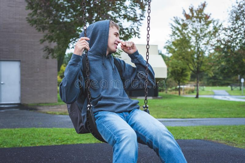Happy teenager on a swing. royalty free stock image