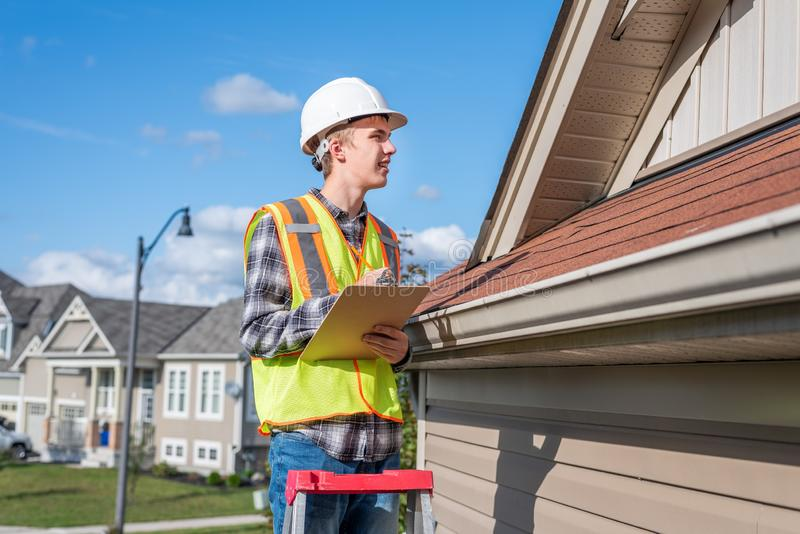 Home inspector providing an inspection to a house. The image displays a home inspector standing on a ladder and providing an inspection to the roof of a house royalty free stock photo