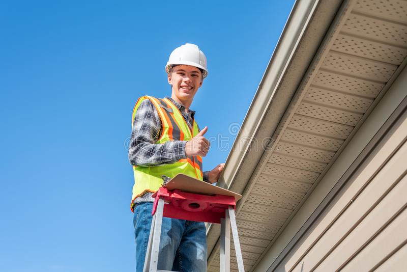 Home inspector providing an inspection to a house. The image displays a home inspector standing on a ladder and providing an inspection to the roof of a house stock photo