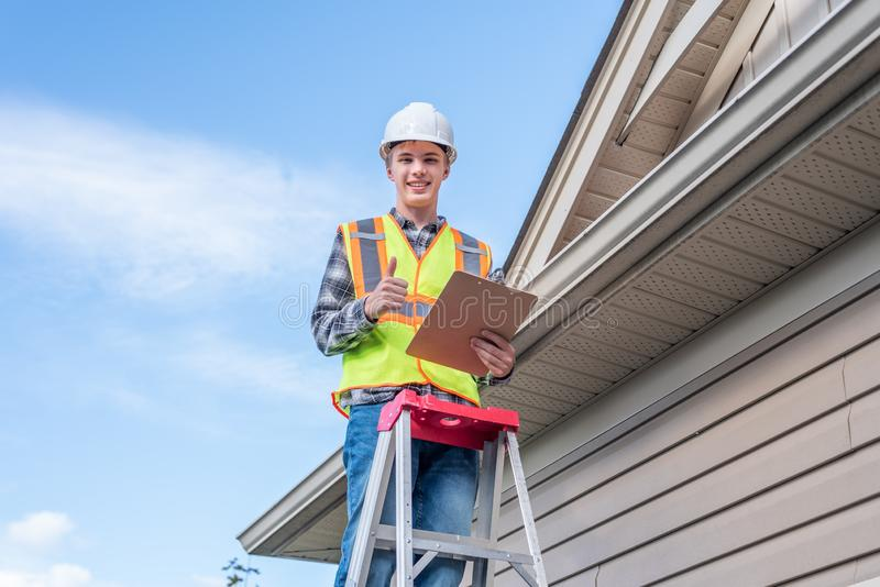 Home inspector providing an inspection to a house. The image displays a home inspector standing on a ladder and providing an inspection to the roof of a house stock photos
