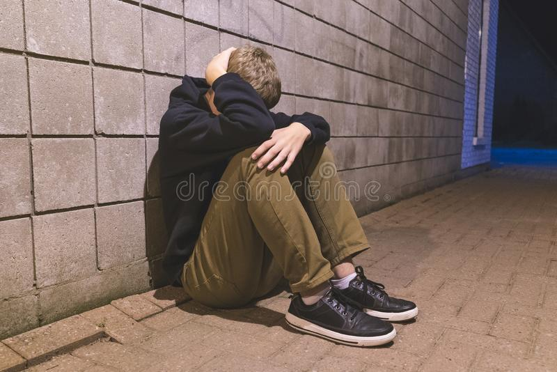 Teenager sitting in an alleyway. royalty free stock photos