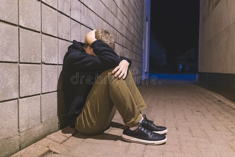 Teenager sitting in an alleyway. royalty free stock photography