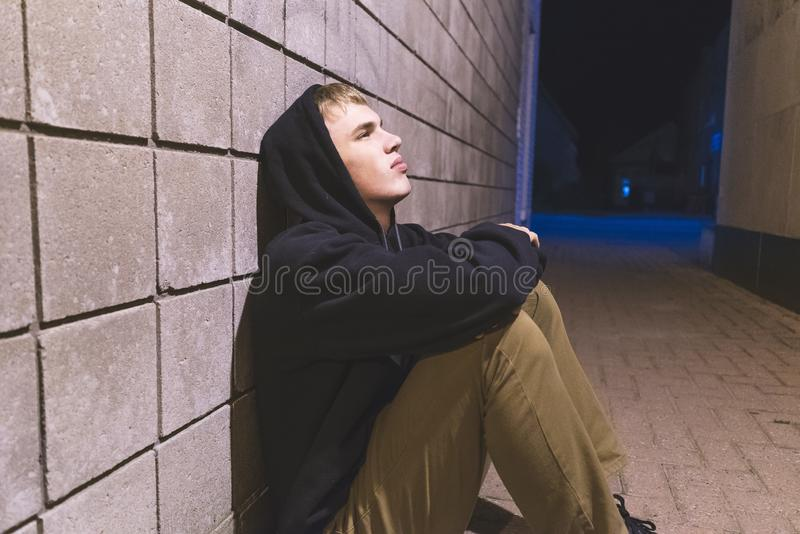 Teenager sitting in an alleyway. royalty free stock images