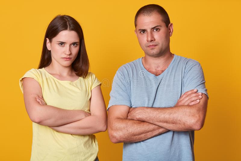 Image of displeased couple looking directly at camera, standing with folded arms, having unpleasant facial expressions, keeping. Silent, not talking to each stock photos