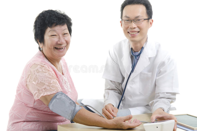 Image of a doctor and his nurse. Checking up a senior patient in the clinic royalty free stock photo