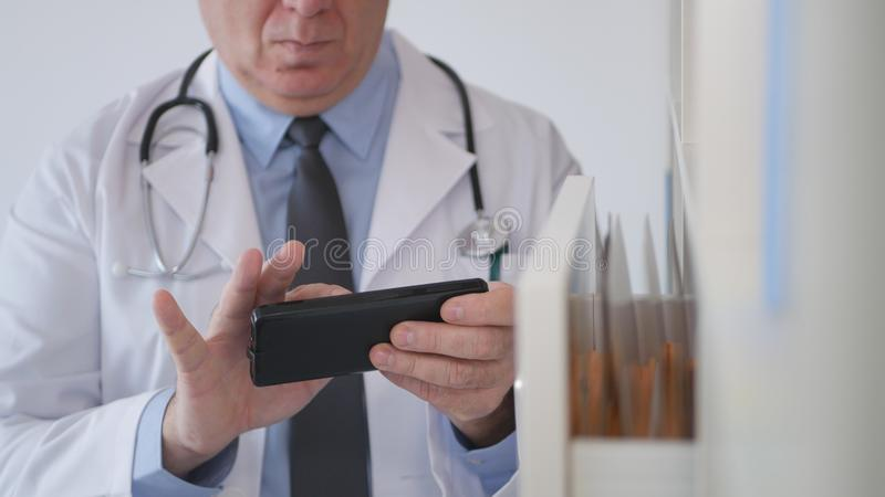 Image with a Doctor Texting on Cellphone in Hospital Cabinet.  stock images