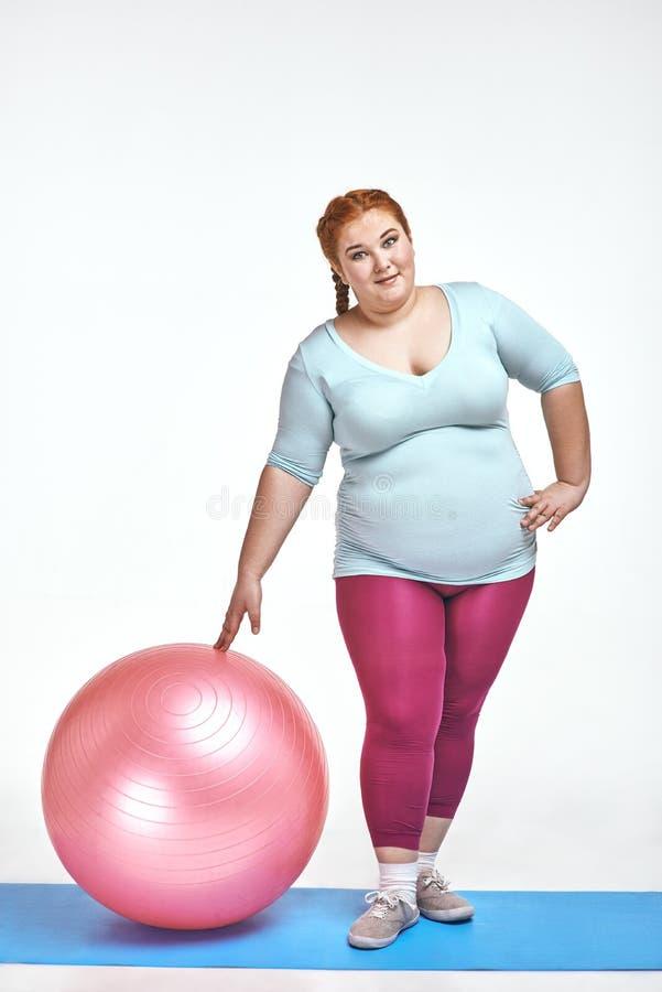 Image drôle d'amuser, femme d'une chevelure et potelée rouge qui tient une boule photos stock
