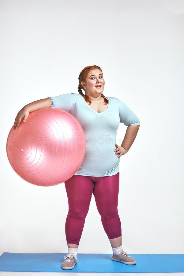 Image drôle d'amuser, femme d'une chevelure et potelée rouge qui tient une boule image stock