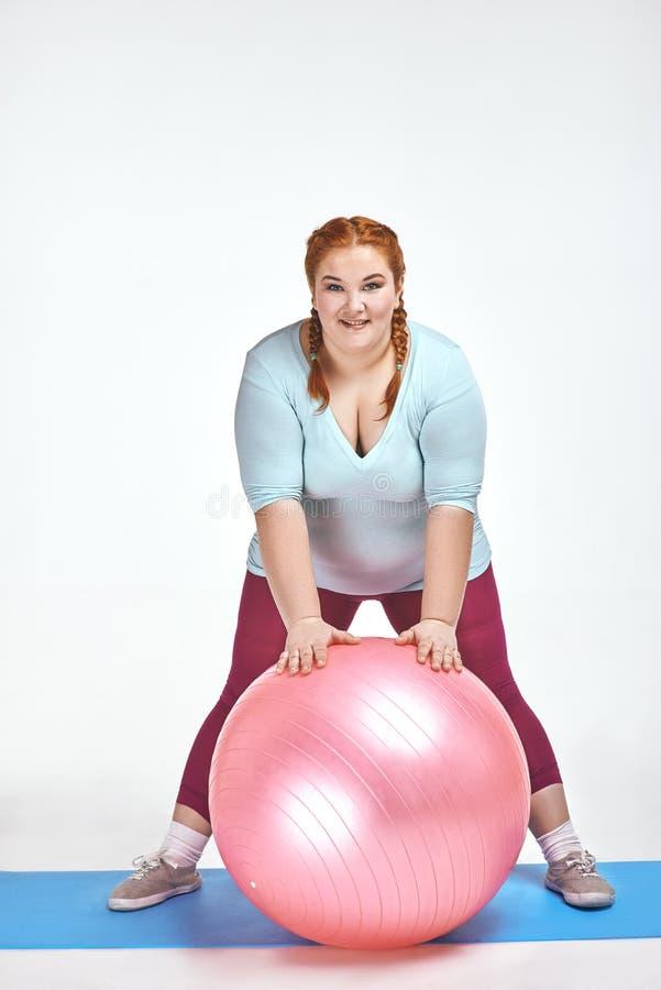 Image drôle d'amuser, femme d'une chevelure et potelée rouge qui tient une boule images libres de droits
