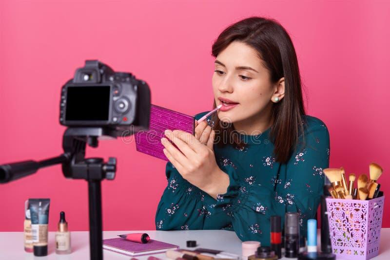 Image du blogger féminin attirant faisant la vidéo pour le blog de beauté, se reposant à la table blanche contre le fond et l'app photo stock