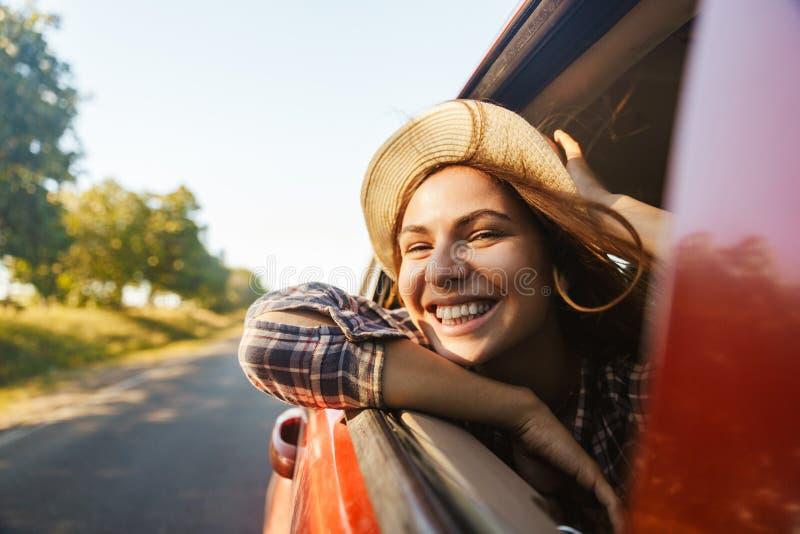 Image du chapeau de paille de port joyeux de la femme 20s souriant et regardant hors de la fenêtre, tout en montant dans la voitu photo stock