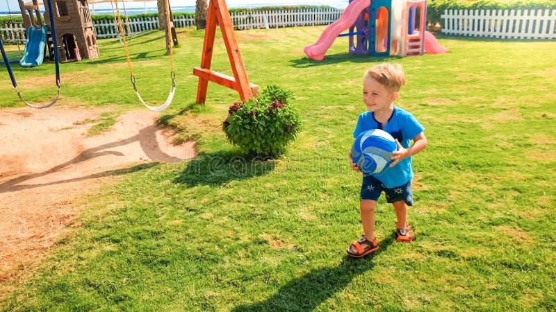 Image du gar?on gai riant heureux tenant la boule du football dans les mains et le fonctionnement sur le terrain de jeu d'enfants image libre de droits
