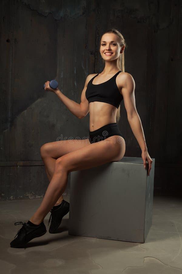 Image du jeune athlète féminin musculaire portant le regard se reposant d'usage noir de sport in camera sur le fond foncé image stock