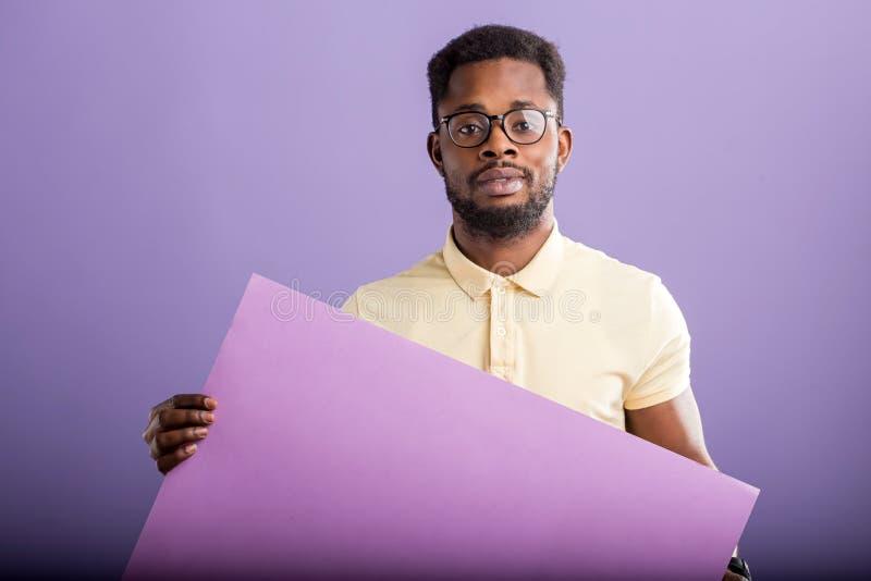 Image du jeune homme d'afro-am?ricain tenant le conseil vide sur le fond violet photos libres de droits